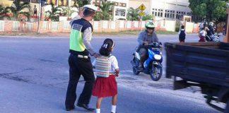 Polisi Membantu Menyebrangkan Anak Sekolah