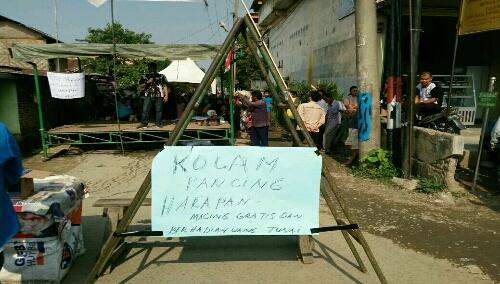 Foto: puluhan warga jalan harapan Desa Buntubedimar, gelar aksi protes jalan rusak dengan gaya memancing ikan di jalan yang sudah berkubang
