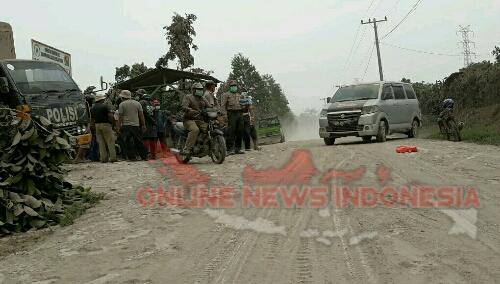 Foto : Aparat Petugas Kepolisian Tanah Karo berjaga Jaga di Zona Merah erupsi Gunung Sinabung dengan Sigap Di Tengah Ketebalan Abu di Badan Jalan