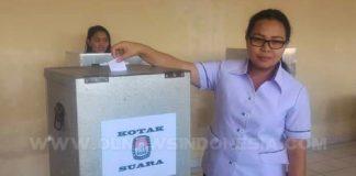 Kepala Sekolah SMA Yadika Langowan Jeiny Sangari SE, memasukan kertas suara di kotak suara dalam pemilihan Ketua Osis periode 2018-2019