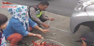 tampak Personil Poslantas Polres Karo, Bribka Sofian Damanik saat memberikan bantuan memperbaiki Ban mobil yang saat rusak di Jln Medan - Berastagi, Selasa (11 /09) 2018