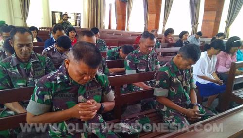 Personil TNI tengah berdoa di dalam gereja.