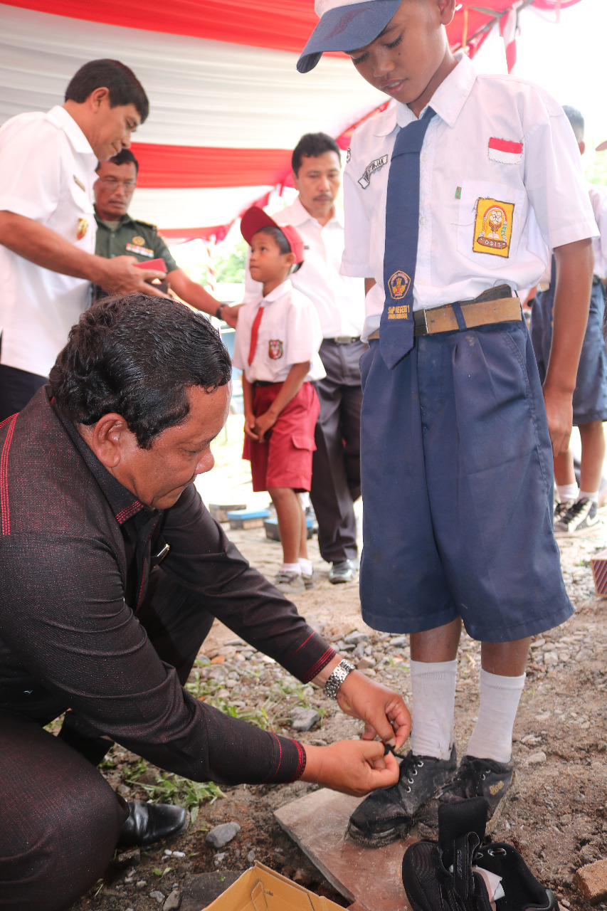 Foto : Pada kesempatan yang sama, Bupati Samosir Drs.Rapidin Simbolon MM memberi dan memakaikan sepatu  bantuan  kepada salah seorang siswa miskin dan anak yatim piatu.