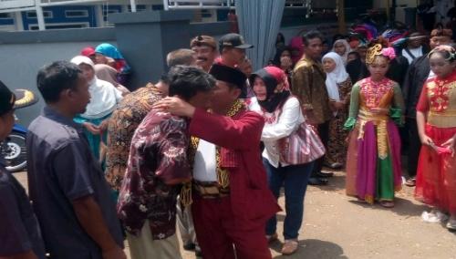 Foto : Kades Sutardi Beserta Istri menyalami warga  hadir dalam acara pelepasan Jabatan Kades yang berakhir masa jabatan,tampak Hadi Sutardi memeluk warga yang menangis haru.