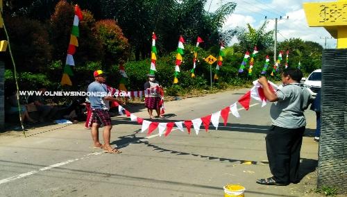 Ket foto  : Tampak Kepala Desa Dokan Martinus Sembiring (baju abu abu) bersama Mahasiswa USU memasang bendera dan umbul umbul untuk menyemarakkan HUT Ke 74 Republik Indonesia.