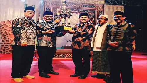 Hasan Basri SE.MM Camat Saketi ( tengah ) saat menerima Piala bergilir Juara Umum yang di serahkan oleh SETDA Kabupaten Pandeglang Feri Hasanudin bertempat di lapangan samping Puskesmas Saketi Rabu malam pukul 22.00, 9/10 .