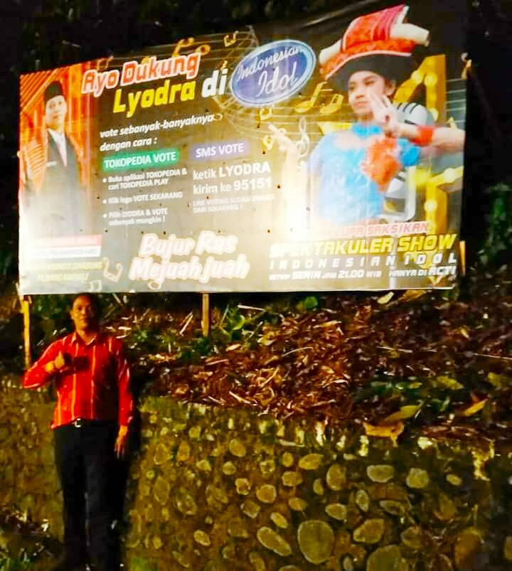 Ket foto : Korindo Sembiring tampak Berdiri di bawah balihonya yang terlihat mendukung Lyodra Margaretha Br Ginting asal Kabupaten Karo yang bertarung dalam pencarian bakat di Indonesian Idol 2020, Sabtu(30/11) 2019 malam (Ist).