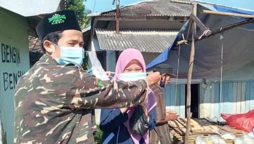 Iman, Ketua PAC Ansor Kecamatan Banjarsari (Kiri), sedang membagikan masker kepada masyarakat.